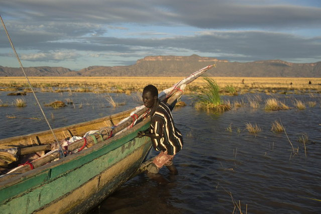 A Turkana man pushes a boat as he prepares to venture onto Lake Turkana for the day's fishing, some kilometres from Todonyang near the Kenya-Ethiopia border in northwestern Kenya October 13, 2013. (Photo by Siegfried Modola/Reuters)