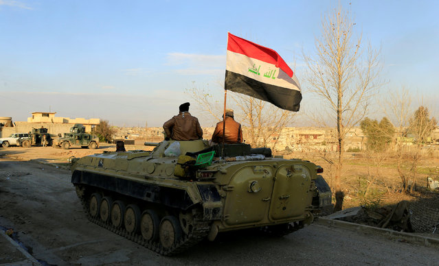 An Iraqi flag is seen on a military vehicle during battle with Islamic State militants in the Mithaq district of eastern Mosul, Iraq, January 3, 2017. (Photo by Thaier Al-Sudani/Reuters)