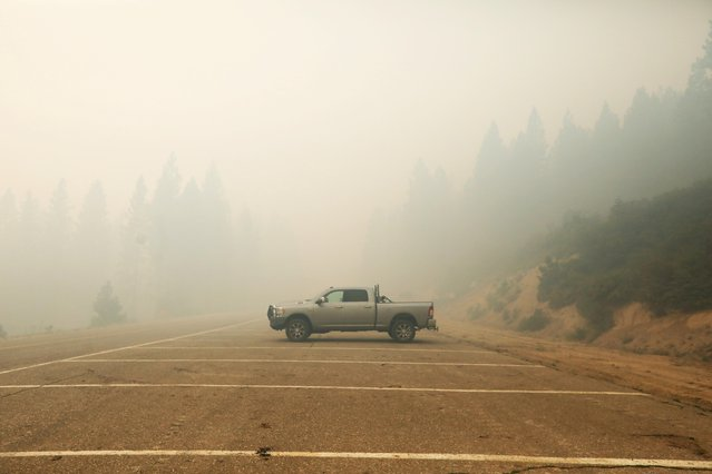 A car stands amongst the smoke from the Dixie Fire along Bucks Lake Road, Meadow Valley, California, U.S., August 1, 2021. (Photo by David Swanson/Reuters)