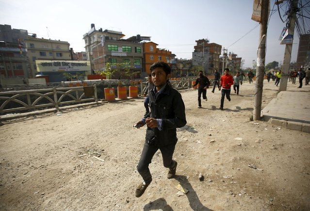 A protester runs to throw a stone towards police personnel and vehicles during a nationwide strike, organised by the opposition alliance led by the Unified Communist Party of Nepal (Maoist) to demand the new constitution be drafted with the consensus of all political parties, in Kathmandu April 7, 2015. (Photo by Navesh Chitrakar/Reuters)