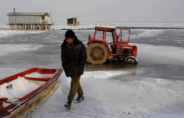 A fisherman walks next to the boat stuck in the frozen Dojran lake, Macedonia January 11, 2017. (Photo by Ognen Teofilovski/Reuters)