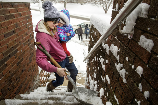 Morgan Miller carries her one-year-old daughter Mia Jennings in one arm as she shovels the stairs to her Springfield home with the other Sunday, January 13, 2019. Miller said she's learned how to do a lot of things while holding a baby in the last year. (Photo by Ted Schurter/The State Journal-Register via AP Photo)