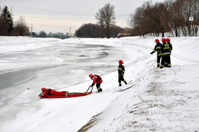 Firemen drag the body of a man out of the Wislok river in Rzeszow, south east Poland, 13 Jabuary 2017. Police confirmed that it is the body of 25-year-old student from a local college, a resident of the Bieszczady region, who disappeared in unclear circumstances in November 2016. (Photo by Darek Delmanowicz/EPA)
