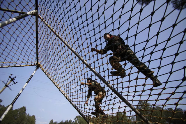 In this December 24, 2013 photo, Indian army soldiers climb an obstacle course during a training session at a battle school in Rajouri, about 138 kilometers (86 miles) northwest of Jammu, India. (Photo by Channi Anand/AP Photo)