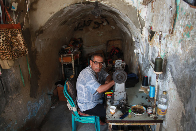 Palestinian tailor Khalil Hamdan, 64, re-sewing worn out shoes and bags for students before the start of the new school year, in light of difficult economic and living conditions for Gazans, at al-Zawya market in Gaza city on August 10, 2021. The fiscal position in Gaza strip has worsened not only due to the outbreak but also due to a political standoff that is disrupting the flow of revenues. The outlook remains precarious and subject to numerous political, security and health risks. (Photo by APAImages/Rex Features/Shutterstock)