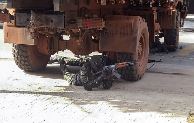 In this image made from video, an unidentified soldier takes up position under a truck near the office of the president in the capital Conakry, Guinea Sunday, September 5, 2021. Guinea's new military leaders sought to tighten their grip on power after overthrowing President Alpha Conde, warning local officials that refusing to appear at a meeting convened Monday would be considered an act of rebellion against the junta. (Photo by AP Photo/Stringer)