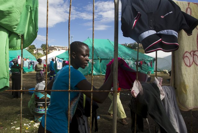 "A foreign woman from Zimbabwe fetches dry clothes from the fence at a camp set up to house those affected by anti-immigrant violence in Chatsworth, north of Durban, April 17, 2015. South Africa sought diplomatic support from countries across the continent on Friday to defeat the ""demon"" of anti-immigrant violence in which at least four people have been killed over the past fortnight. (Photo by Rogan Ward/Reuters)"
