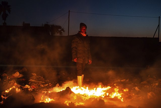A man warms himself from a fire in dumped rubble during a sudden cold front near Johannesburg, Saturday, August 28, 2021. (Photo by Ali Greeff/AP Photo)