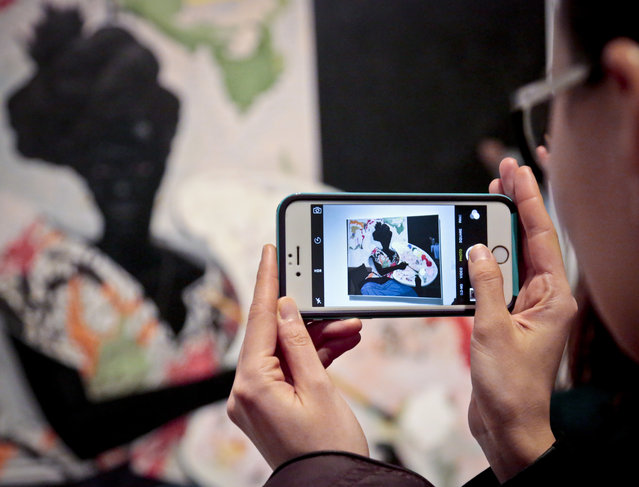 """A visitor photographs American artist Kerry James Marshall's 2009 """"Untitled"""" acrylic painting, during a press preview for the inaugural exhibition at The Met Breuer museum, Tuesday, March 1, 2016, in New York. The Metropolitan Museum of Art throws open the doors March 18 to its new modern and contemporary art outpost, The Met Breuer.  The new space is a short walk from the Met's Fifth Avenue headquarters. (Photo by Bebeto Matthews/AP Photo)"""