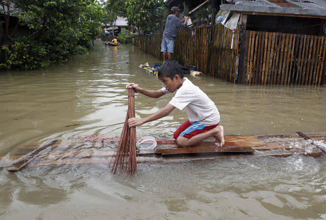 A boy uses a broom to paddle a makeshift raft along a flooded road in Butuan city in southern Philippine island of Mindanao January 17, 2014. The death toll from the floods and landslides in Mindanao caused by a lingering low-pressure area climbed to 34 on Friday, while more than 300,000 people are displaced due to flooding and landslides, the National Disaster Risk Reduction and Management Council reported. (Photo by Erik De Castro/Reuters)