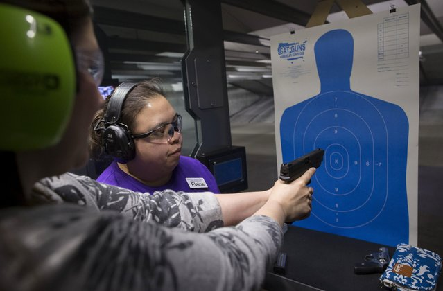 Instructor Elaine Campo-Oplanic (R) gives advice on how to hold a firearm during a meeting of The Well Armed Woman Shooting Chapters at GAT Guns in East Dundee, Illinois, April 21, 2015. (Photo by Jim Young/Reuters)