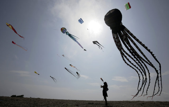 A girl is looking at kites during First Varvara Kite Fest in the village of Varvara on Bulgarian Black Sea coast, some 450 km Southeast from Sofia, Friday, August 27, 2021. Varvara Kite Fest organiser Andrey Kulev says that flying a kite is like releasing all your problems in the sky. (Photo by Valentina Petrova/AP Photo)