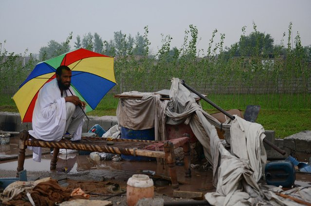 A Pakistani resident sits alongside with his belongings following heavy rain and winds in Peshawar on April 27, 2015. (Photo by A. Majeed/AFP Photo)