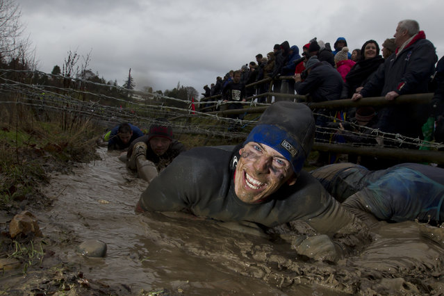 """A competitor makes his way through an obstacle during the annual Tough Guy race – """"the toughest race in the world"""" – at Perton in Staffordshire, England, Sunday Jan. 26, 2014. (Photo by Jon Super/AP Photo)"""