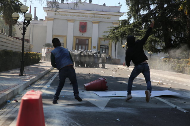 Protesters throw stones at riot police as thousands of opposition supporters protest in Tirana, Albania on Saturday, March 16, 2019. (Photo by Visar Kryeziu/AP Photo)