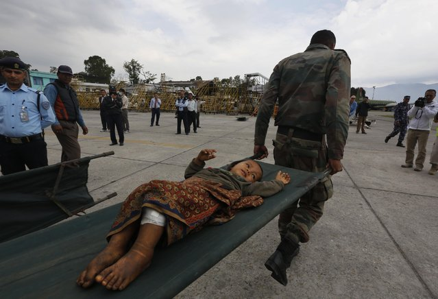 A Nepalese child injured in Saturday's earthquake is taken on a stretcher after being evacuated from higher reaches of mountains by Nepalese army soldiers, in Kathmandu, Nepal, Wednesday, April 29, 2015. (Photo by Manish Swarup/AP Photo)