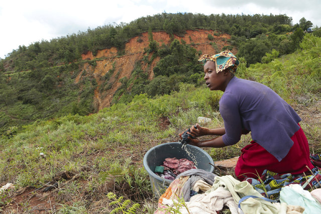 A woman does her laundry near a mountain where a mudslide caused by Cyclone Idai killed several people in Chimanimani about 600 kilometres south east of Harare, Zimbabwe, Tuesday March 19, 2019. According to the government, Cyclone Idai has killed more than 100 people in Chipinge and Chimanimani and according to residents the figures could be higher because the hardest hit areas are still inaccessible. Some hundreds are dead, many more are missing, and some thousands at risk from the massive flooding throughout the region of Mozambique, Malawi and Zimbabwe caused by Cyclone Idai. (Photo by Tsvangirayi Mukwazhi/AP Photo)