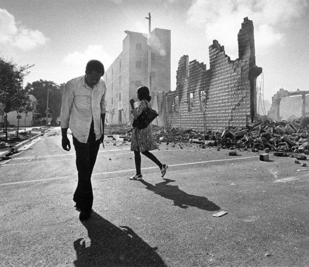 In this May 19, 1980, photo, people walk past ruins in the Culmer section of Miami after rioting over the acquittal of four police officers charged with the 1979 beating death of Arthur McDuffie, a black motorcyclist. When future Virginia Gov. Ralph Northam and future Attorney General Mark Herring admitted dressing up in blackface in the 1980s racial stereotypes and racist imagery in popular culture seemed to be everywhere. There also was racial unrest and historic elections of black mayors. (Photo by Kathy Willens/AP Photo)