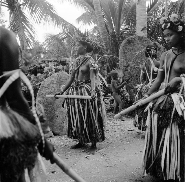 circa 1955:  A traditional bamboo dance on the island of Yap, part of the Caroline Islands in the western Pacific Ocean. Behind the dancers are large stone discs with a hole in the centre, the traditional form of currency on the island.  (Photo by Mary Knoll/Three Lions/Getty Images)