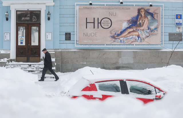 A mens walks on a snow covered street in Kiev, Ukraine, 06 February 2017. Snowfalls, wind and temperatures of down to minus 20 degrees Celsius are forecast by weather officials in Ukraine for the next days. (Photo by Sergey Dolzhenko/EPA)