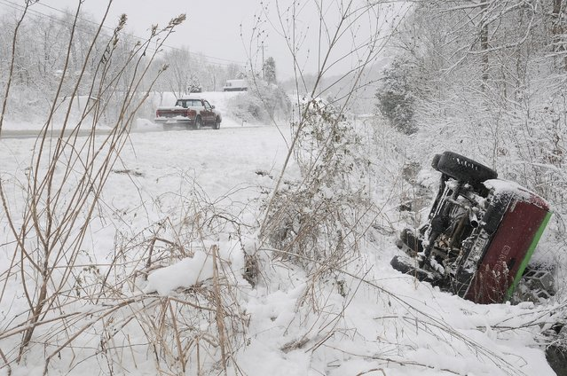 An abandoned truck sits on it's side in a shallow creek along Chapman Highway in Sevier County Thursday, February 13, 2014, near Sevierville, Tenn. Emergency personnel checked the truck and then moved on to more pressing matters as reports of 3-10 inches of snow fell overnight. (Photo by Curt Habraken/AP Photo/The Mountain Press)