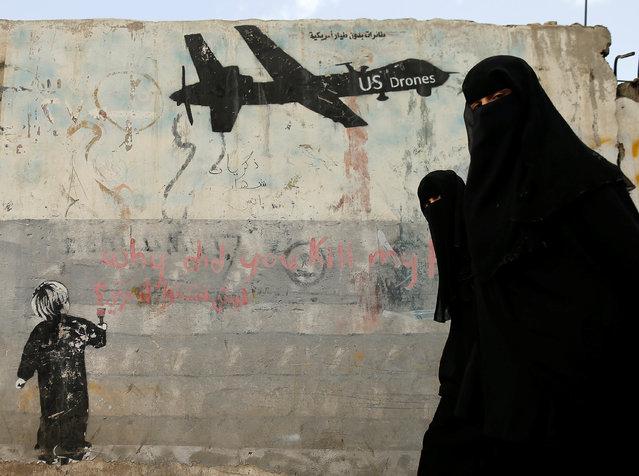 Women walk past a graffiti, denouncing strikes by U.S. drones in Yemen, painted on a wall in Sanaa, Yemen February 6, 2017. (Photo by Khaled Abdullah/Reuters)