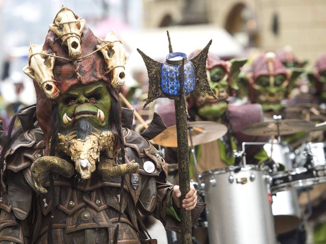 Strange characters with fantastic masks and costumes parade along the narrow streets while groups of carnival musicians blow their instruments in joyful cacophony and thousands of bizarrely clad people dance away the spirits of winter. (Photo by Sigi Tischler/Keystone)