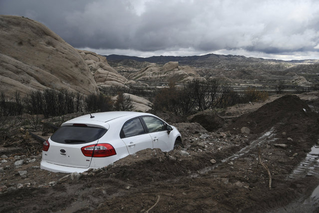 An abandoned Kia sedan is seen stuck in heavy mud in Lone Pine Canyon Road near Highway 138 in Phelan, Calif., on Saturday, February 18, 2017. (Photo by David Pardo/The Daily Press via AP Photo)