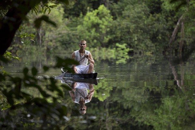 Kambeba Indian, Dream Braga (R), 18, rows his canoe near the village Tres Unidos, Amazon state May 9, 2015. (Photo by Bruno Kelly/Reuters)