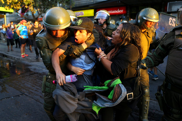 A protester is detained during a rally marking the anniversary of the death of union leader Juan Pablo Jimenez, in Santiago, Chile February 21, 2017. (Photo by Ivan Alvarado/Reuters)