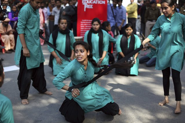 A group of college girls perform a street play on violence against women, to mark International Women's Day in New Delhi, India, Saturday, March 8, 2014. (Photo by Tsering Topgyal/AP Photo)