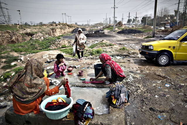 Pakistani women, wash their laundry at a water reservoir, on the outskirts of Islamabad, Pakistan, Thursday, March 20, 2014. The United Nations has proclaimed that March 20 is the International Day of Happiness. (Photo by Muhammed Muheisen/AP Photo)