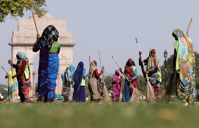 Municipal workers sweep the front lawns of India Gate war memorial in New Delhi, India, April 13, 2016. (Photo by Anindito Mukherjee/Reuters)