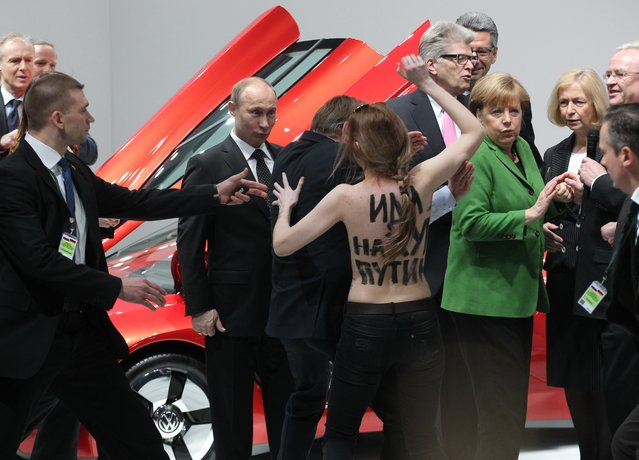 "Russian President Vladimir Putin (C) is attacked by an activist of the Ukrainian women rights group ""Femen"" as German Chancellor Angela Merkel (R) looks on during their visit of the industrial exhibition ""Hannover Messe"" on April 8, 2013 in Hannover, Germany. (Photo by Sasha Mordovets/Getty Images)"