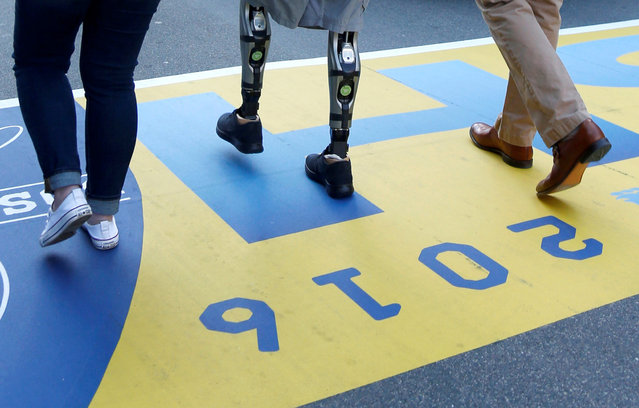 Marathon bombing survivor Jeff Bauman walks across the finish line after a wreath laying ceremony at the sites of the Boston Marathon bombings on Boylston Street in Boston, Massachusetts, April 15, 2016. (Photo by Mary Schwalm/Reuters)