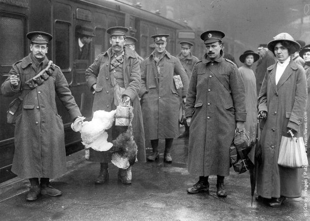 1914: Soldiers, including two recruits who have brought some chickens, at Victoria prepare to board the train for the battle front