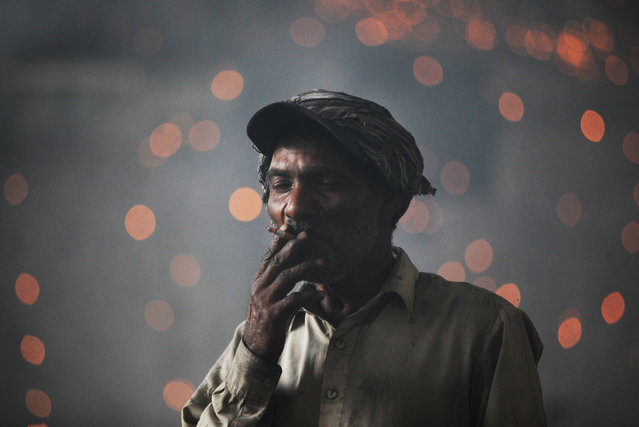 A laborer smokes a cigarette as he takes a break while working in a foundry, ahead of Labor Day, in Lahore, Pakistan on April 30, 2019. (Photo by Mohsin Raza/Reuters)