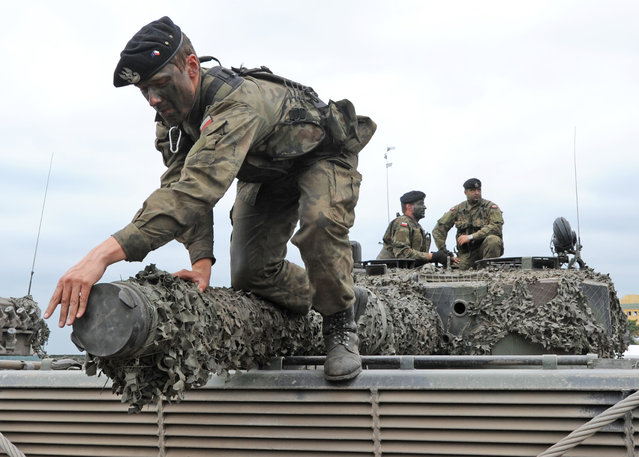 A Polish Army soldier covers the barrel of a tank after the NATO Noble Jump exercise on a training range near Swietoszow Zagan, Poland, Thursday, June 18, 2015. (AP Photo/Alik Keplicz)
