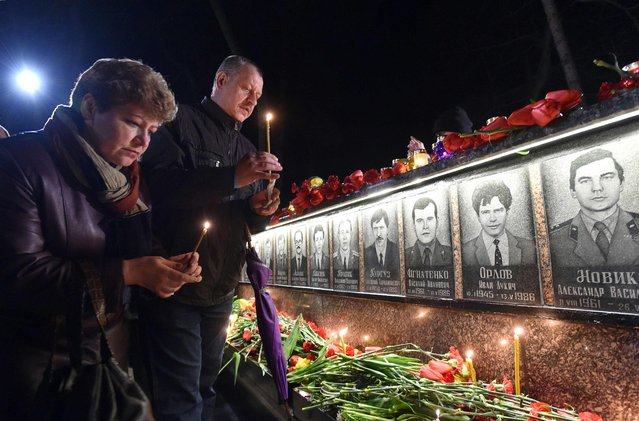 People hold candles in front of the monument to Chernobyl victims in Slavutich, some 50 kilometres (30 miles) from the accident site, and where many of the power station's personnel used to live, during a memorial ceremony early on April 26, 2016. Ukraine on April 26 marked the 30th anniversary of the Chernobyl disaster, the world's worst nuclear accident. (Photo by Genya Savilov/AFP Photo)