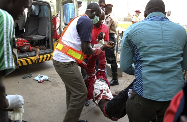 A Red Cross worker and other volunteers help move a body into the mortuary of the Asokoro General Hospital after a bomb blast, in Abjua April 14, 2014. (Photo by Afolabi Sotunde/Reuters)