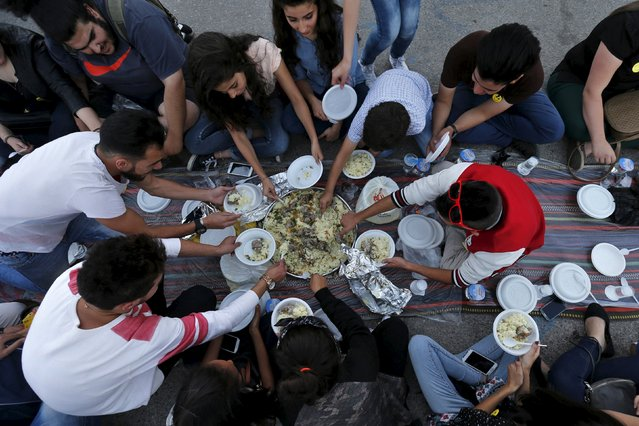 "People eat their Iftar (breaking of fast) during a local initiative called ""Let's Have Iftar Together"" during the holy fasting month of Ramadan in Amman, Jordan June 27, 2015. (Photo by Muhammad Hamed/Reuters)"