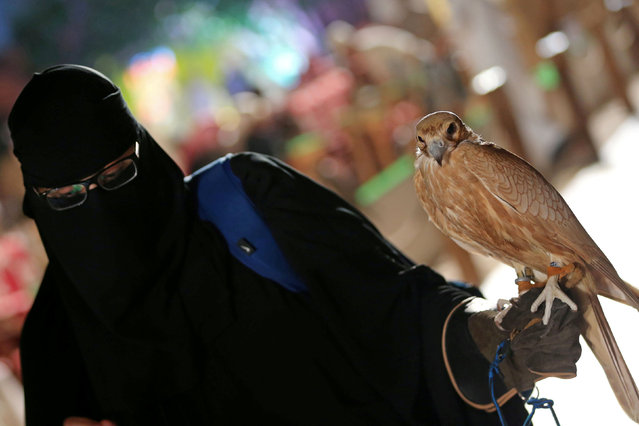 A woman holds a falcon at the first Saudi Falcons and Hunting Exhibition in Riyadh, Saudi Arabia, December 5, 2018. (Photo by Reuters/Stringer)
