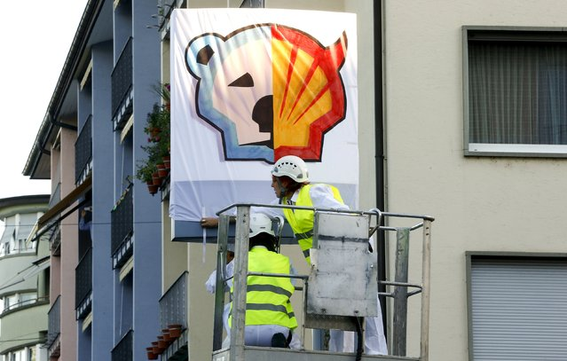 Members of Greenpeace put a banner over the company logo at a Shell gas station during a protest in Zurich, June 30, 2015. (Photo by Arnd Wiegmann/Reuters)