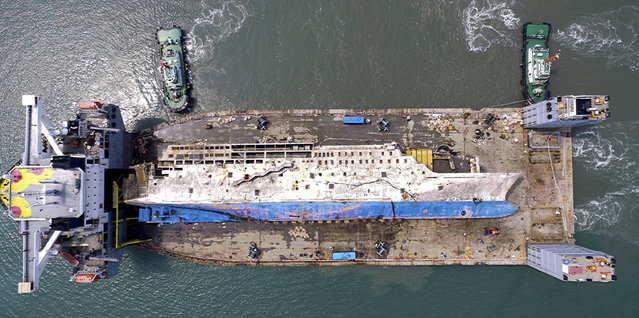 The sunken ferry Sewol is seen on a semi-submersible transport vessel in waters off Mokpo, South Korea. Friday, March 31, 2017. The corroding 6,800-ton ferry raised from the bottom of the sea last week arrived at a South Korean port Friday, where it will be searched for the remains of nine missing passengers from a 2014 sinking. (Photo by Kim Do-hun/Yonhap via AP Photo)