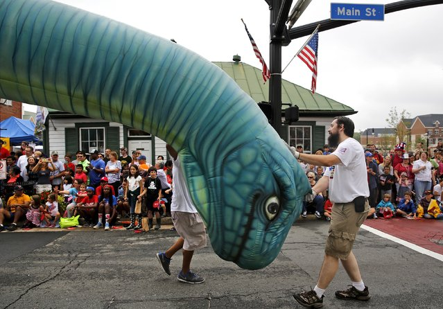 A team from Woody's Ice Cream shop wrangle a large inflatable dinosaur down the street during the Independence Day Parade in Fairfax, Virginia July 4, 2015. (Photo by Jonathan Ernst/Reuters)