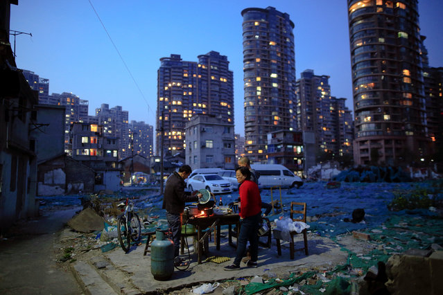 Jiang Wei cooks dinner outside a six-square-meter house he rents with a friend, at Guangfuli neighbourhood in Shanghai, China, March 28, 2016. Jiang and his friend rent the house with a monthly rent of 450 yuan for two years. (Photo by Aly Song/Reuters)