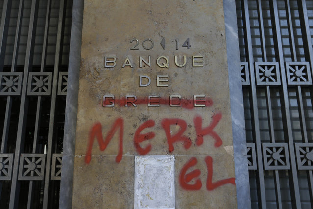 """Red spray paint covers a French-language Bank of Greece sign to read """"Bank of Merkel"""" in reference to German Chancellor Angela Merkel in Athens, Monday, July 6, 2015. Greek Finance Minister Yanis Varoufakis resigned Monday, saying he was told shortly after Greece's decisive referendum result that some other eurozone finance ministers and the country's other creditors would appreciate his not attending the ministers' meetings. (Photo by Thanassis Stavrakis/AP Photo)"""