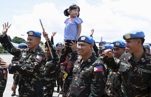 A Philippines soldier deploying to the United Nations peacekeeping mission in Haiti, holds up his daughter during a sending-off ceremony at the Villamor air base in Pasay city, Metro Manila July 7, 2015. (Photo by Erik De Castro/Reuters)