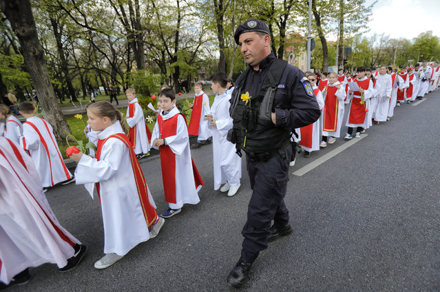 In this Sunday, April 9, 2017, picture a gendarme with a flowers attached to his uniform walks next to Catholic children taking part in a Palm Sunday procession in Bucharest, Romania. (Photo by Vadim Ghirda/AP Photo)