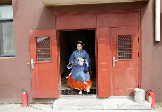 """Li Doudou, dressed in """"Hanfu"""", or Han clothing, leaves an apartment block for a performance of the """"guqin"""" traditional musical instrument, an ancient seven-stringed zither, in Hebei province, China, August 18, 2019. (Photo by Jason Lee/Reuters)"""